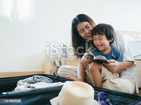 Young asian woman and little baby boy preparing for road trip at home.