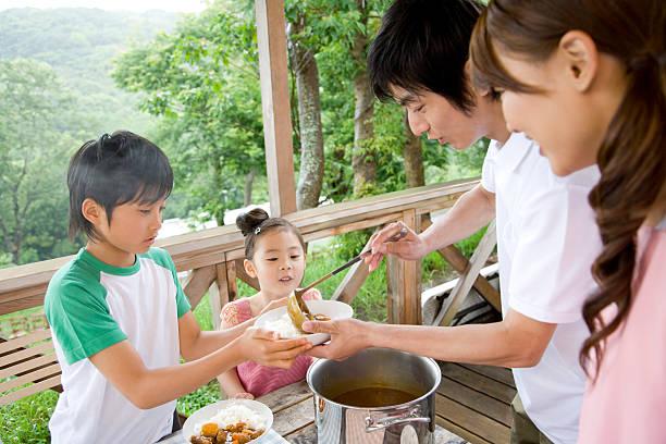 Familia preparando una comida en la terraza de madera - foto de stock
