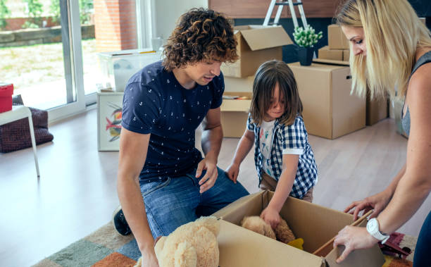 family preparing moving toy box - happy mom packing some toys stock photos and pictures