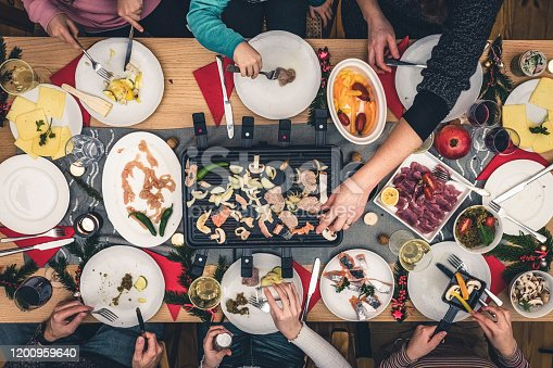 overhead view on family sitting around wooden table with raclette grill