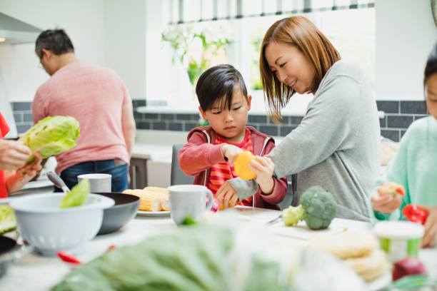 family preparing vegetables for a stir fry - kids cooking stock photos and pictures