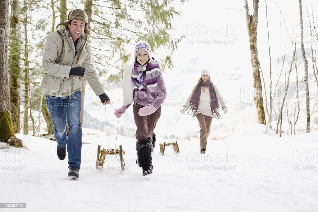 Family pulling sleds through snow stock photo