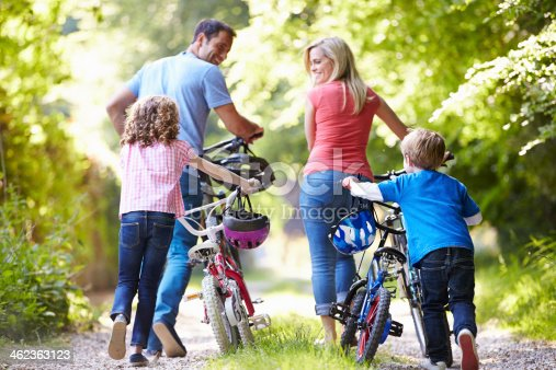 istock Family Pushing Bikes Along Country Track 462363123