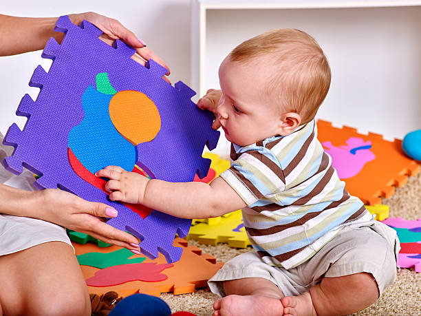 Family puzzle making mother and baby. Child jigsaw develops children. – Foto