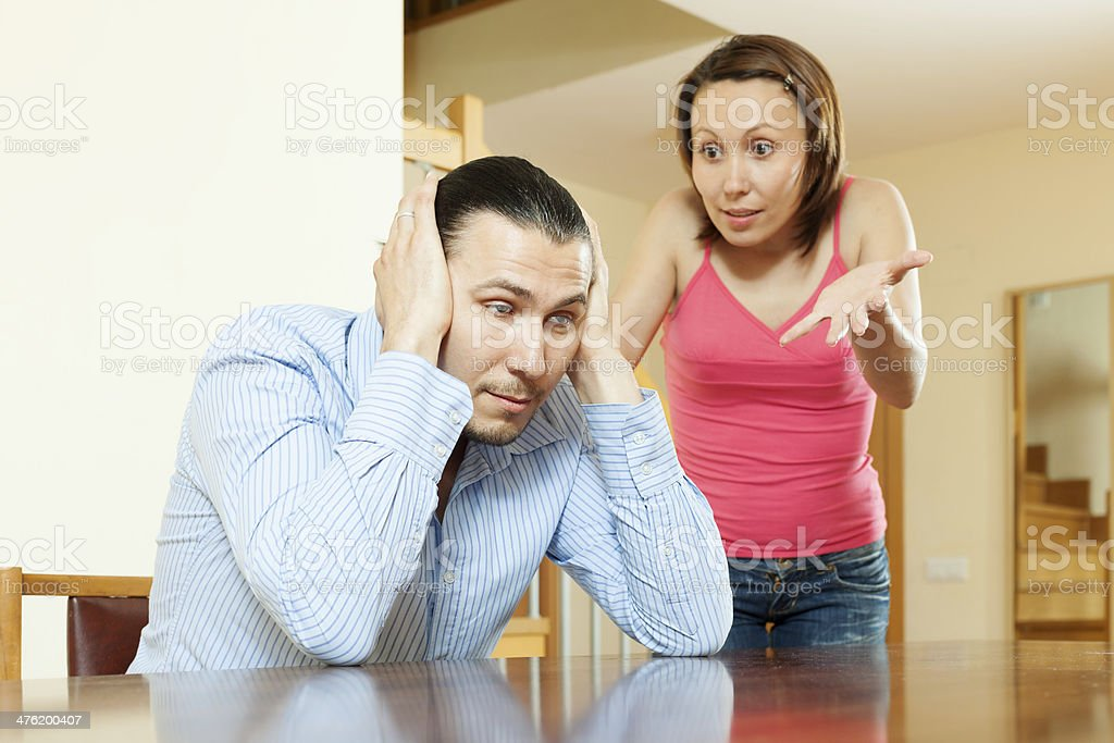 Family quarrel. Tired man listening to his angry wife royalty-free stock photo