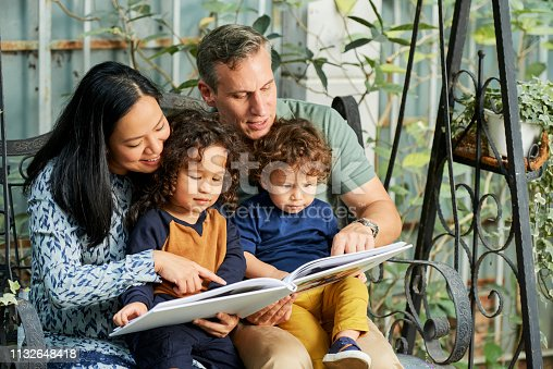 Happy family of four reading book of fairy tales together