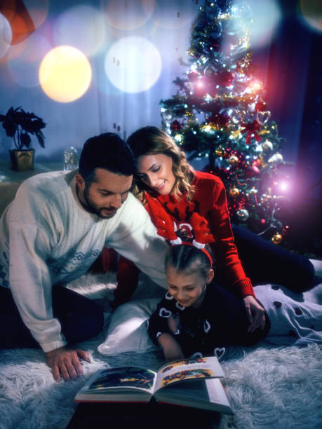 familie lesung a christmas story - nikolaus geschichte stock-fotos und bilder