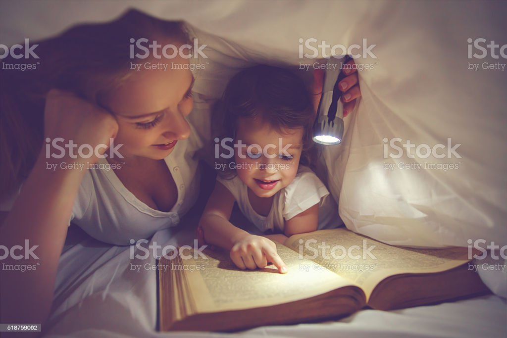 Family reading bedtime. Mom and child daughter reading a book with a...