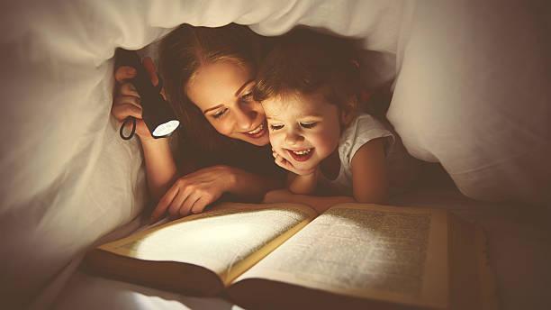 familie lesung in der nacht. mutter und kind liest buch - deckenleuchte kinderzimmer stock-fotos und bilder