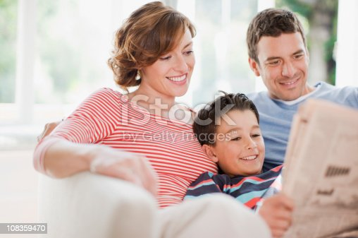 istock Family reading newspaper together 108359470