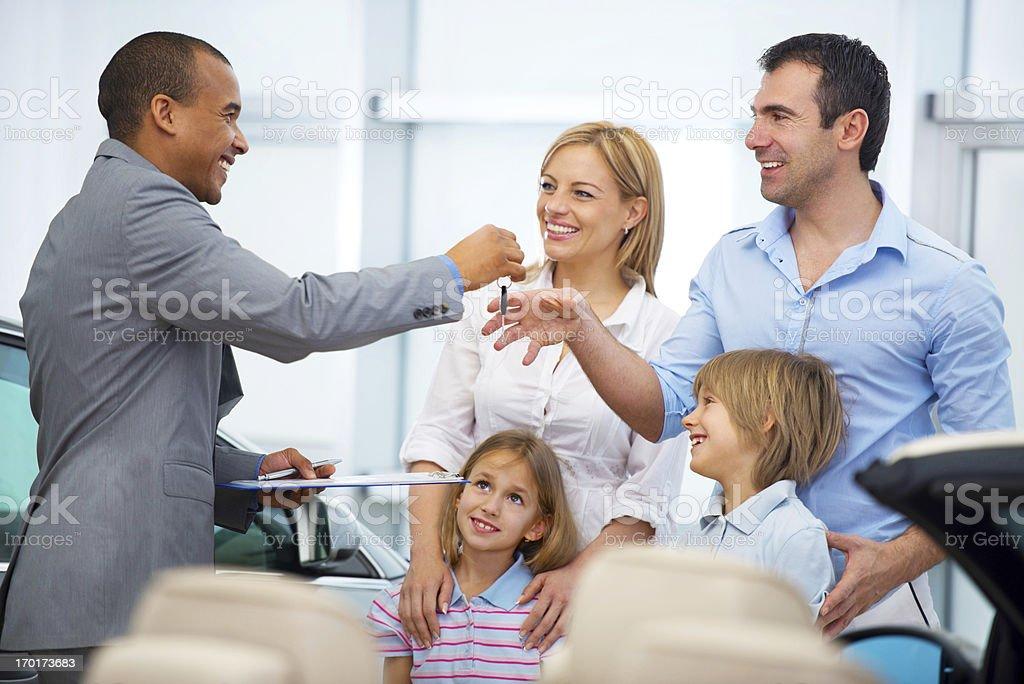Family receiving a new car keys. stock photo
