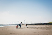 Asian family playing in the beach where there is wind power station in the background.