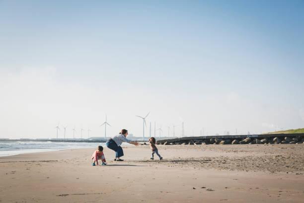 Família relaxada na praia perto de parque eólico - foto de acervo