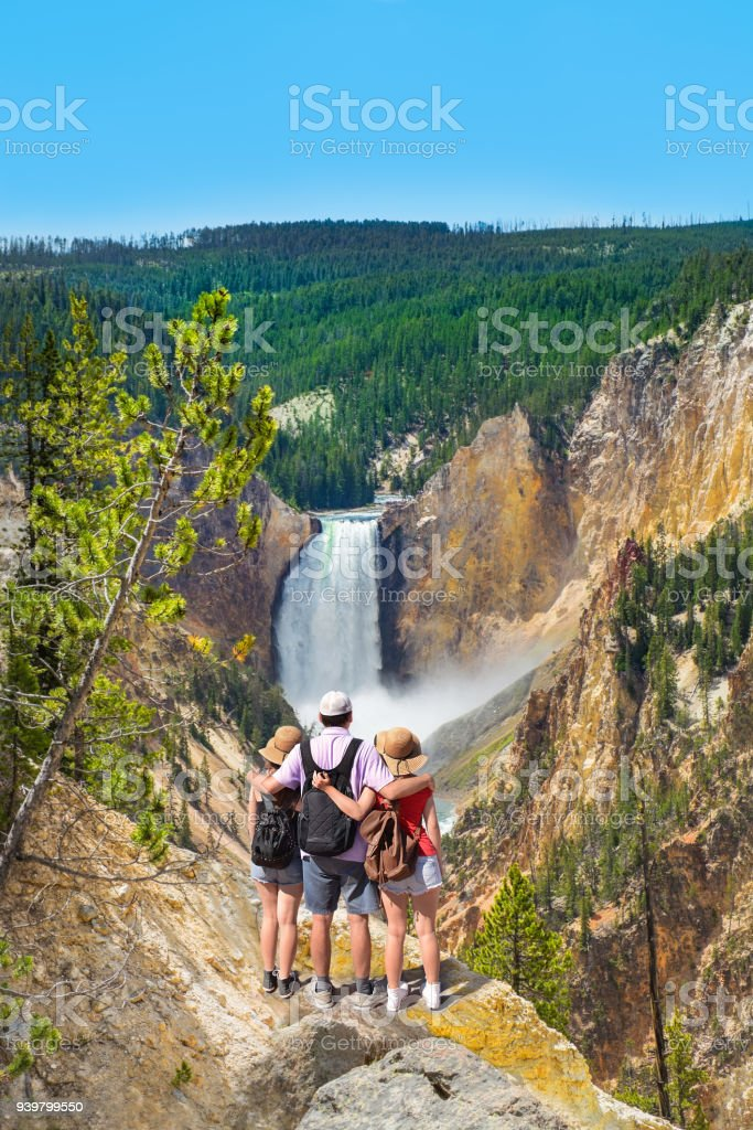 Family relaxing and enjoying beautiful view of waterfall on hiking trip in the mountains. stock photo
