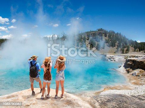 Family relaxing and enjoying beautiful view of gazer on vacation hiking trip. Friends on hiking trip. Excelsior Geyser from the Midway Basin in Yellowstone National Park. Wyoming, USA