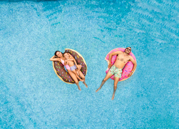 Family relaxing at swimming pool Family relaxing at swimming pool floating on water stock pictures, royalty-free photos & images