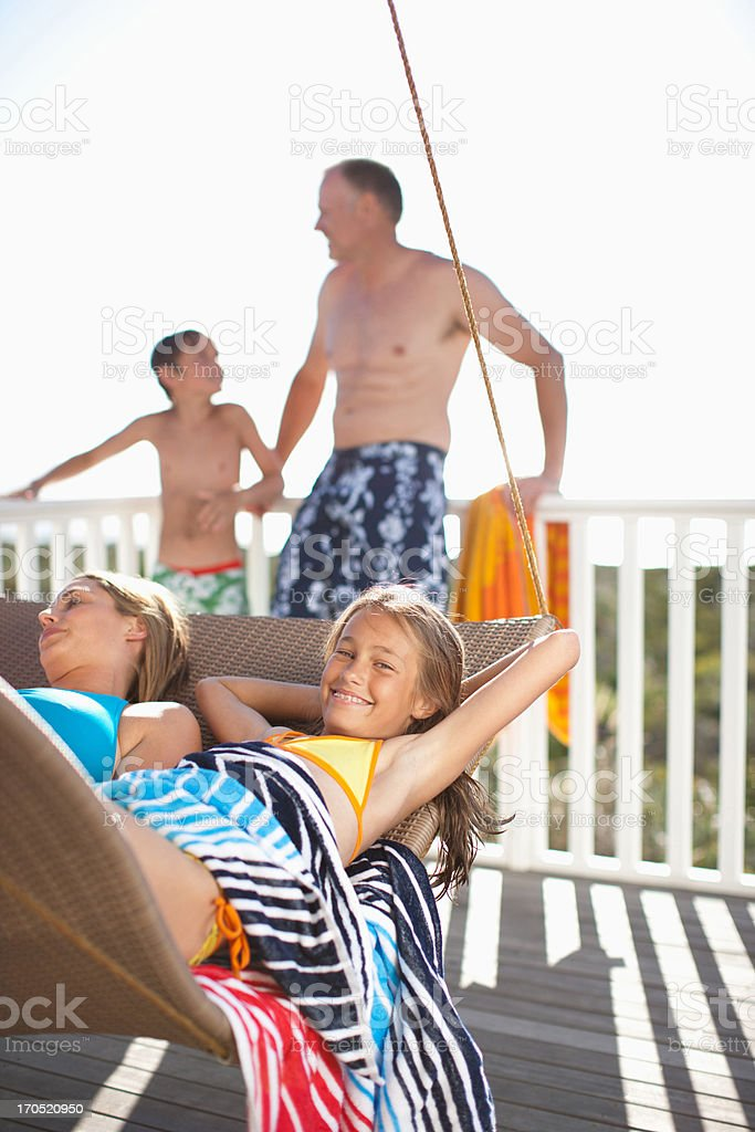 Family relaxing on lounge chair on deck royalty-free stock photo