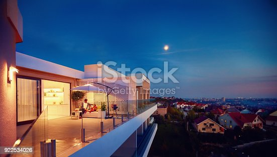 istock family relaxing on roof top patio with evening city view 922534026