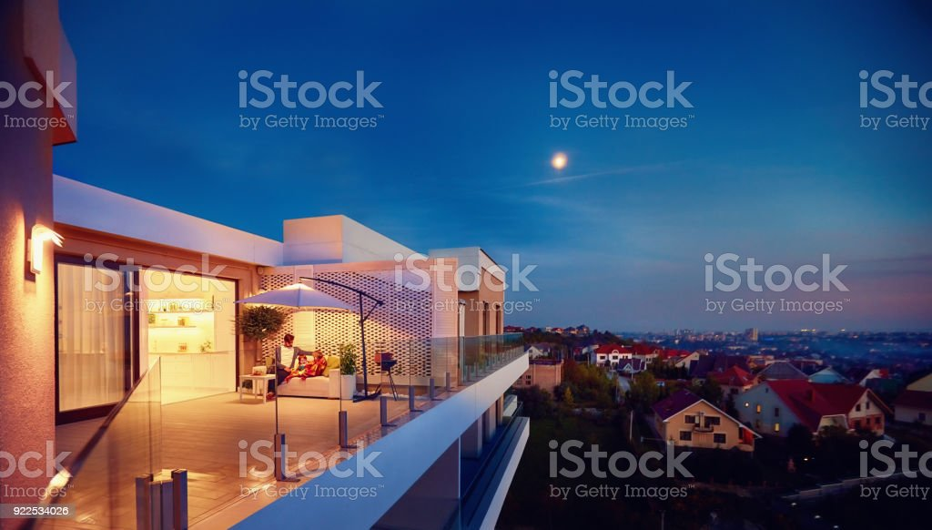 family relaxing on roof top patio with evening city view stock photo