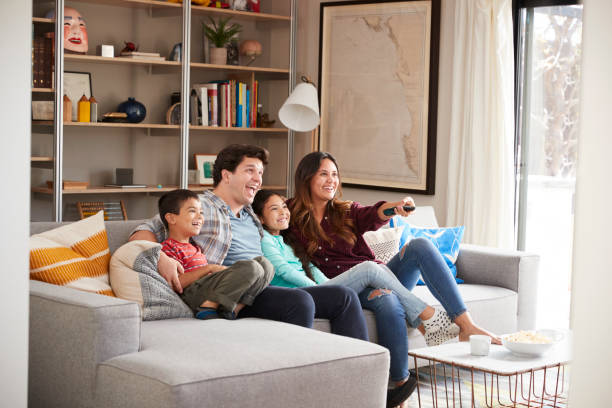 family relaxing on sofa at home watching television - family room stock photos and pictures