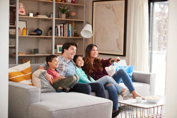 家族が自宅でテレビでソファーでリラックス ストックフォト