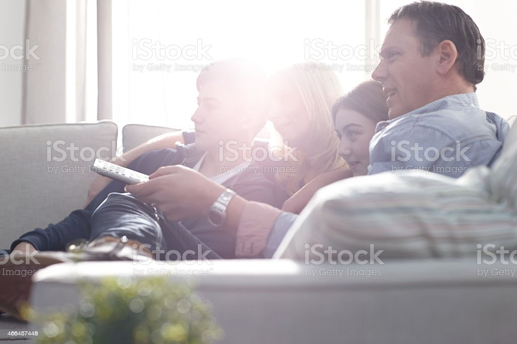 Family relaxing on sofa watching television stock photo