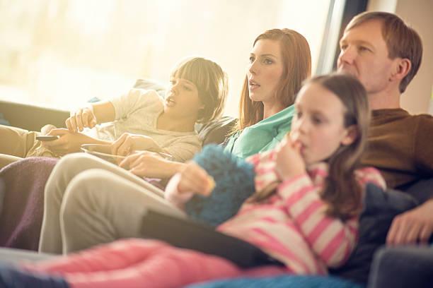 familie entspannend auf sofa fernsehen - mädchen night snacks stock-fotos und bilder