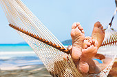 family relaxing on the beach in hammock, exotic holidays travel, closeup of feet