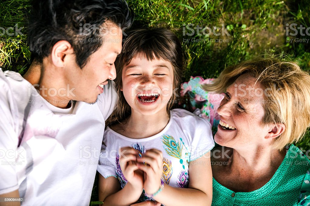 Family relaxing on the grass in a Kyoto city park stock photo