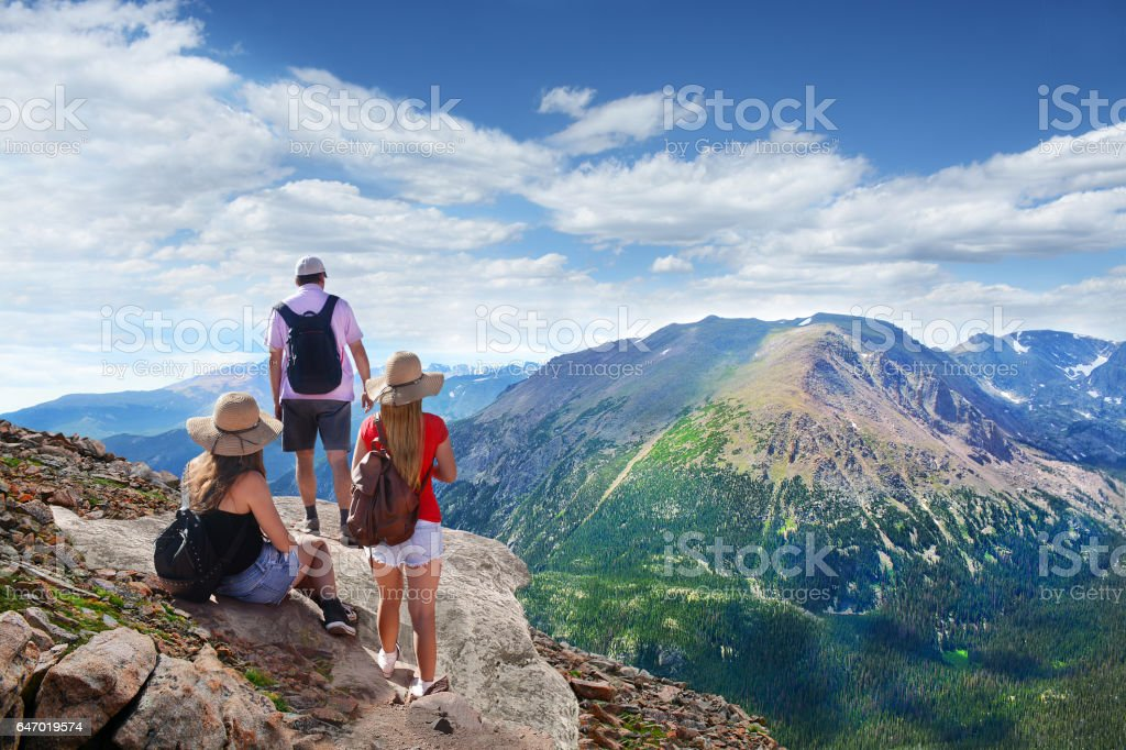 Family relaxing on top of the beautiful mountain. stock photo