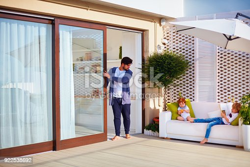 istock family relaxing outdoor on rooftop patio with open space kitchen and sliding doors 922538692