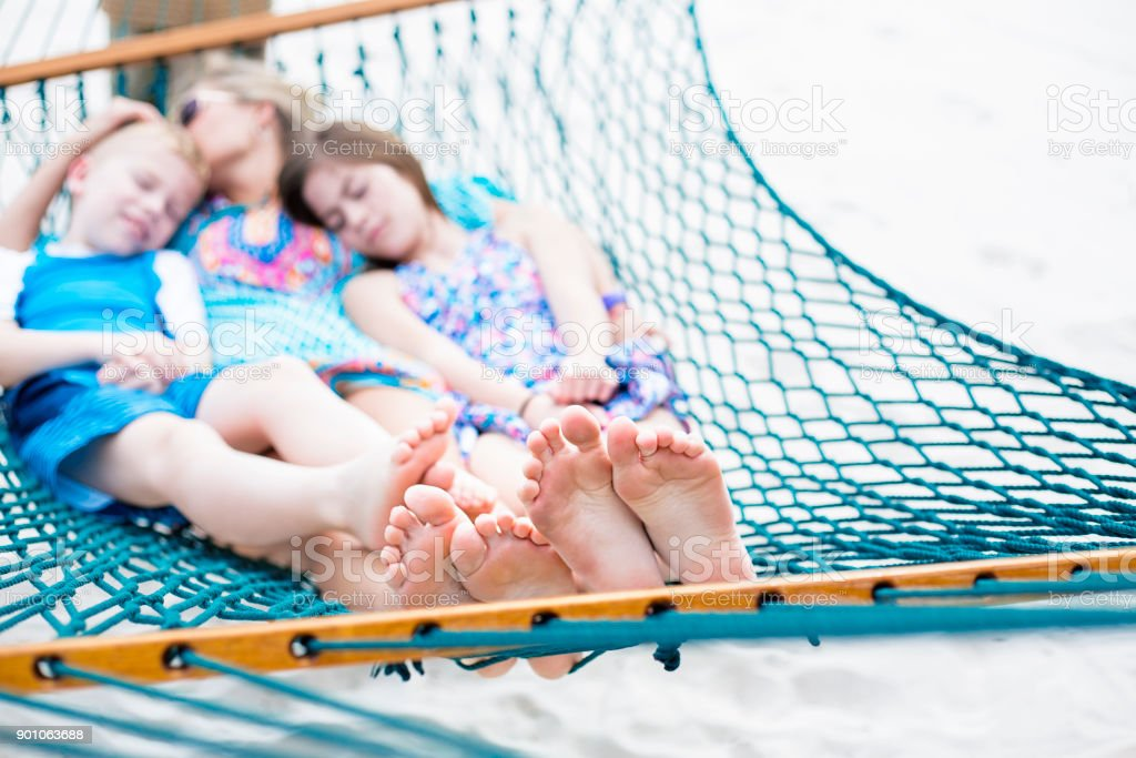 Family relaxing together on a hammock, focus on feet stock photo