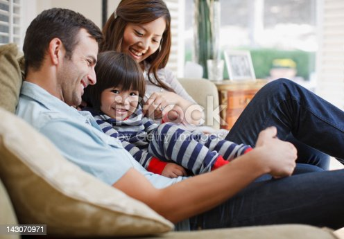 istock Family relaxing together on sofa 143070971