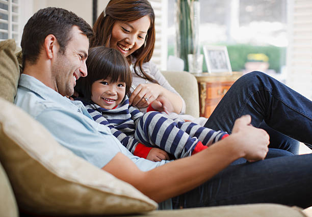 Family relaxing together on sofa stock photo