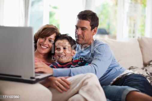 istock Family relaxing together on sofa 171102350