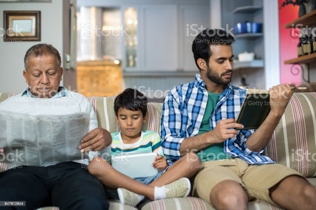 Family relaxing while sitting on sofa stock photo