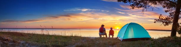 Family resting with tent in nature at sunset stock photo
