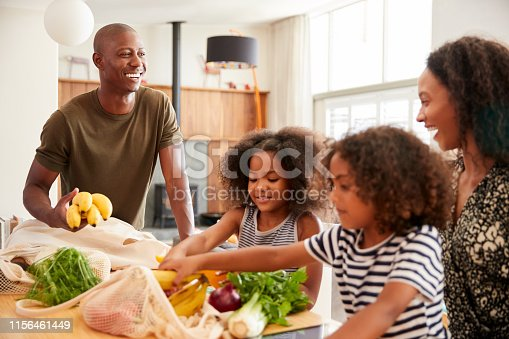 Family Returning Home From Shopping Trip Unpacking Plastic Free Grocery Bags