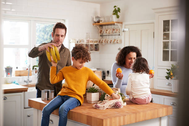 family returning home from shopping trip using plastic free bags unpacking groceries in kitchen - grocery home foto e immagini stock