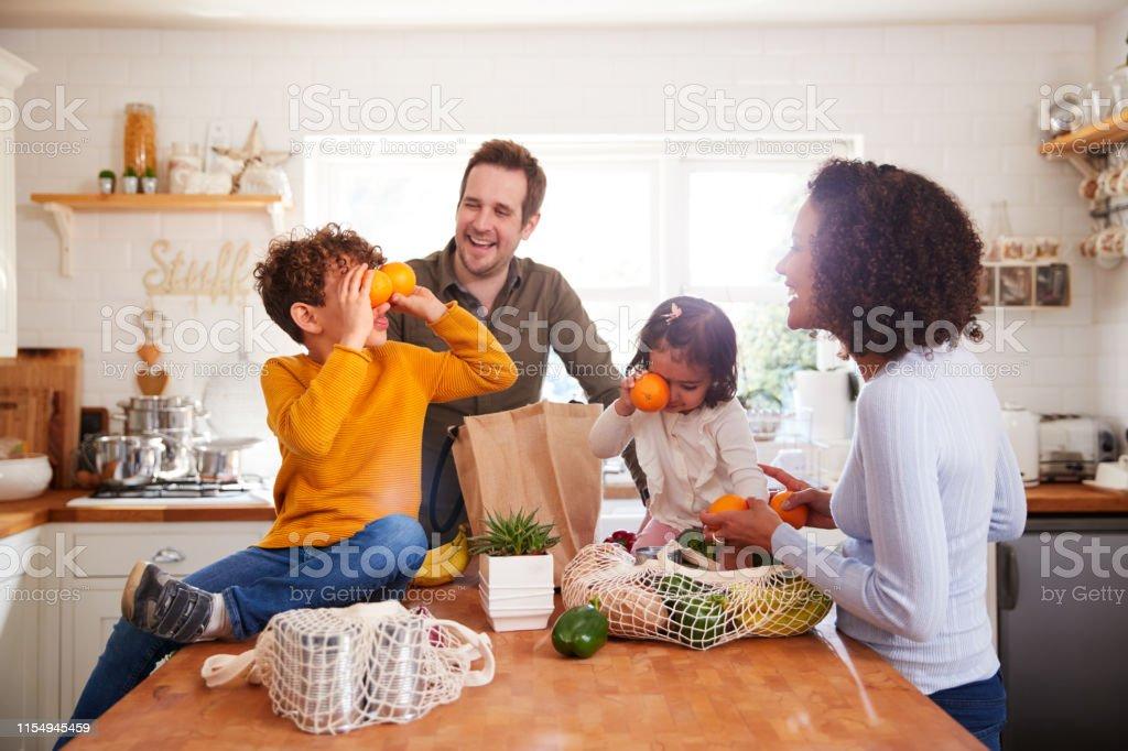 家庭從購物之旅回家使用塑膠免費袋在廚房裡打開雜貨 - 免版稅30多歲圖庫照片