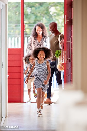 670900812 istock photo Family Returning Home From Shopping Trip Using Plastic Free Grocery Bags Opening Front Door 1156459805
