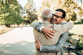 Family reunion. Father and son hugging outdoors.