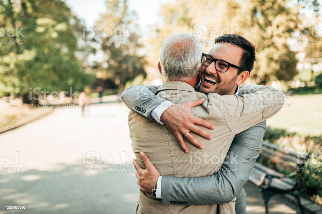 Family reunion. Father and son hugging outdoors. stock photo