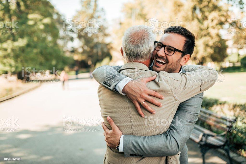 Familientreffen. Vater und Sohn umarmt im Freien. – Foto