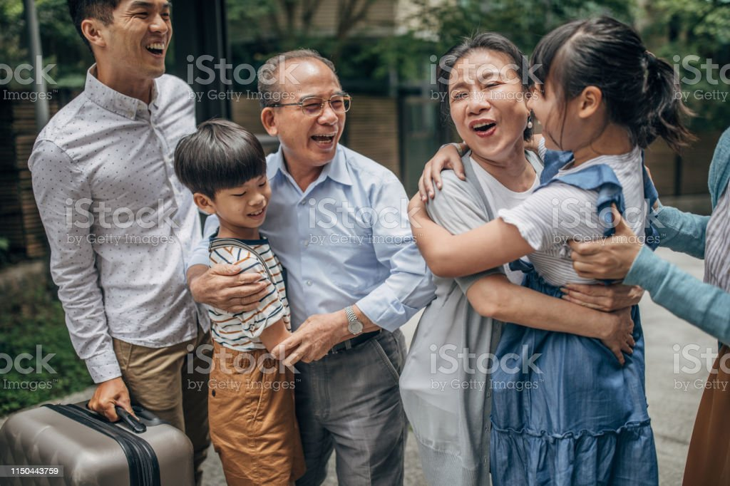 Family reunion with grandparents Group of people greeting each other in front of the house, two kids with mother and father came to visit their grandparents. Active Seniors Stock Photo