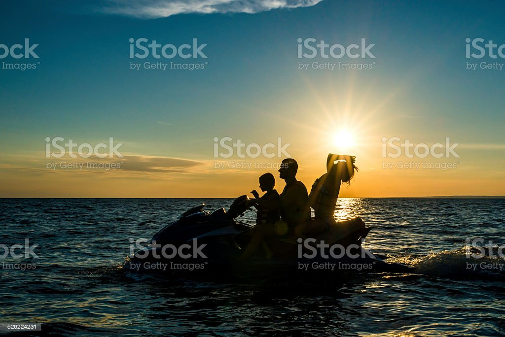 Family Riding a Jet Boat at Sunset stock photo