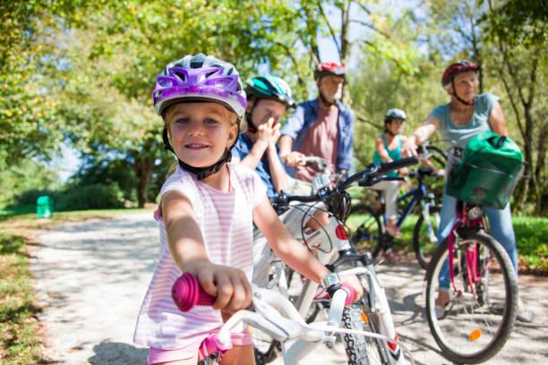 familie reiten fahrrad im park - kinderfahrrad stock-fotos und bilder