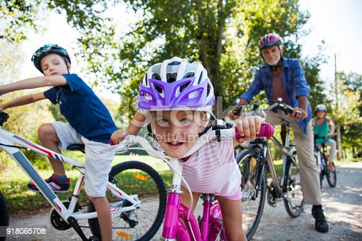 Family enjoying and riding bicycle on dirt track in park.