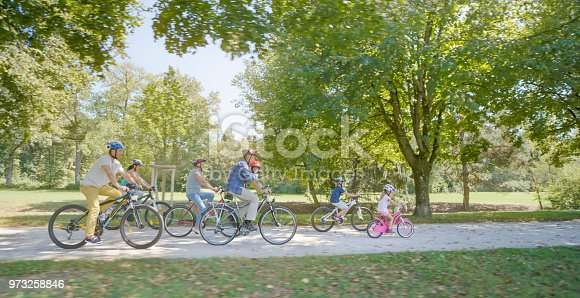 Family riding bicycle on dirt track in park.