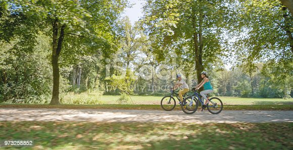 Mid adult couple riding bicycle in park.